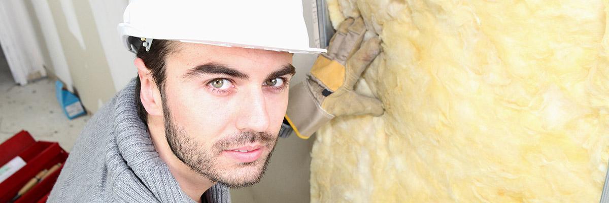 un jeune homme en tenue de chantier est en train de poser de la laine de verre