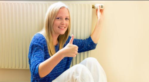 une dame assise devant un chauffage règle le thermostat en souriant