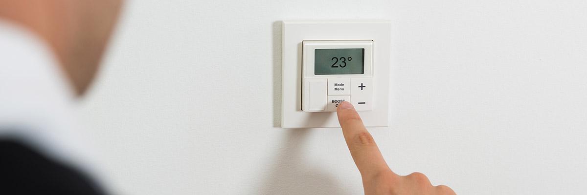 un doigt posé sur un thermostat intérieur