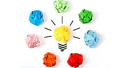 Une ampoule est entourée de boules de papier de différentes couleurs