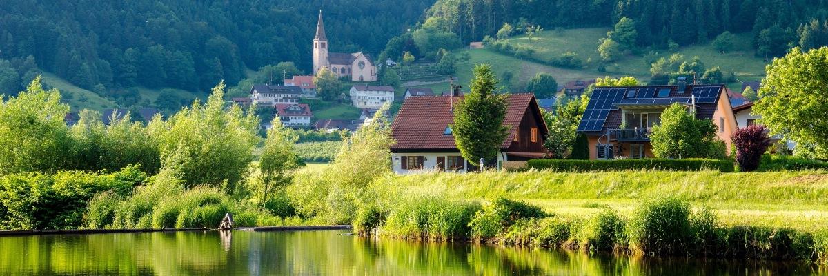 Deux maisons dont l'une avec des panneaux photovoltaïques devant un lac pendant le printemps avec un paysage vert.