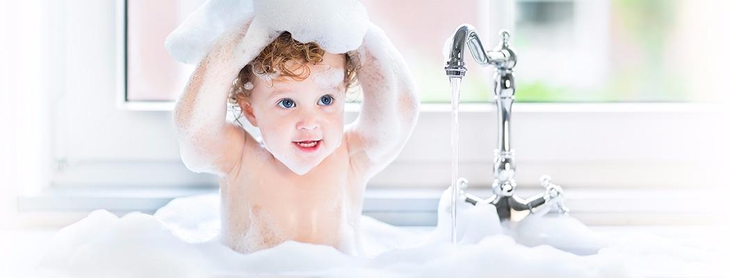 un petit garçon prend un bain, il est entouré de mousse