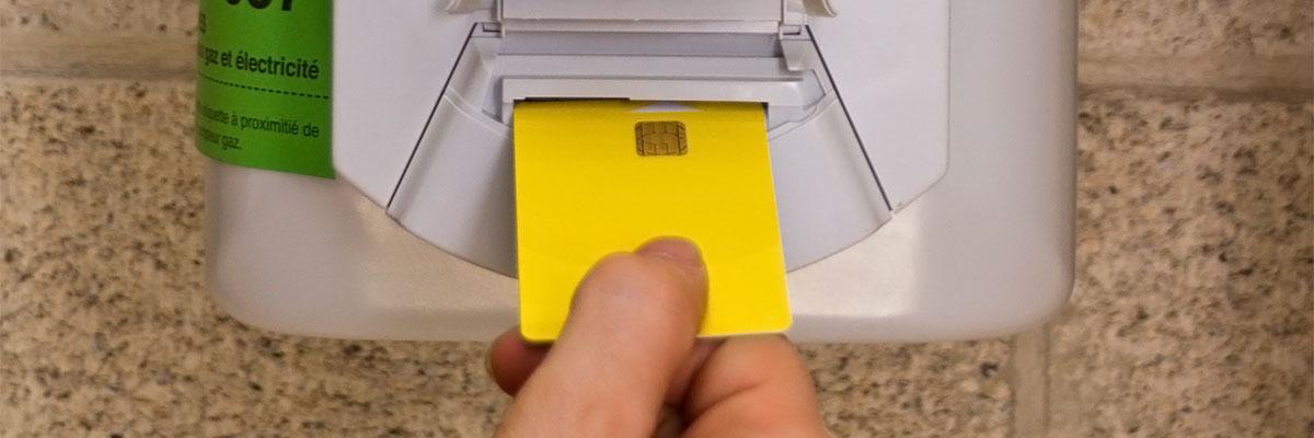 une personne insére une carte dans un compteur à budget gaz