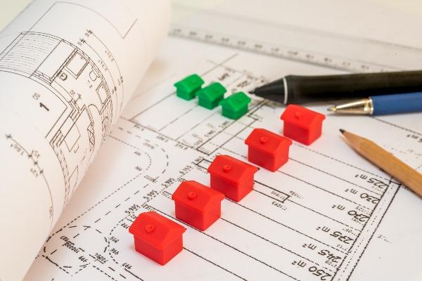 plans de lotissement illustrés avec des petites maisons en plastique rouges et vertes