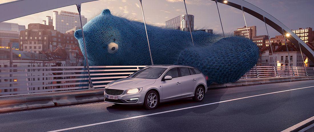 un ours bleu pousse une voiture CNG pour lui permettre de traverser un pont