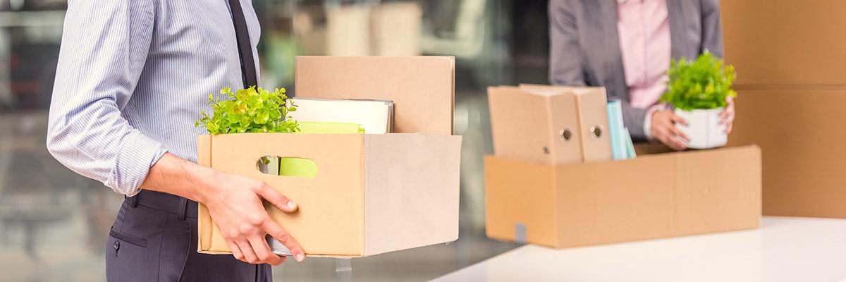 Deux employés de bureau sont en train de déménager leurs affaires dans la bonne humeur