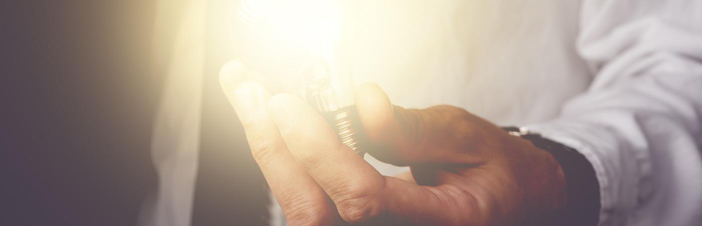 Une main tient une ampoule allumée