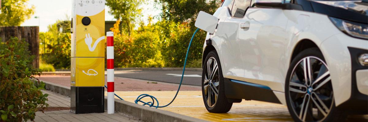 Une voiture blanche est en train de faire le plein via une borne de recharge électrique
