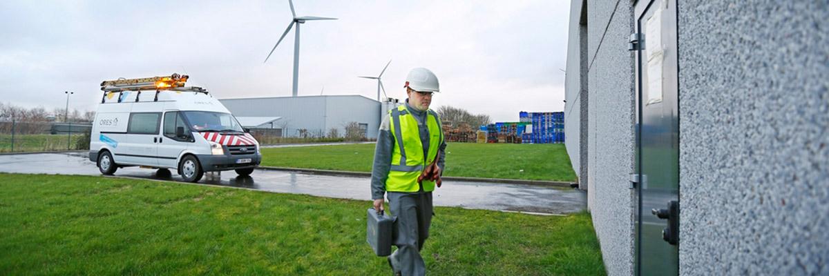 un collaborateur ORES s'apprête à intervenir dans un bâtiment industriel. En arrière plan, on voit la camionnette ORES et des éoliennes