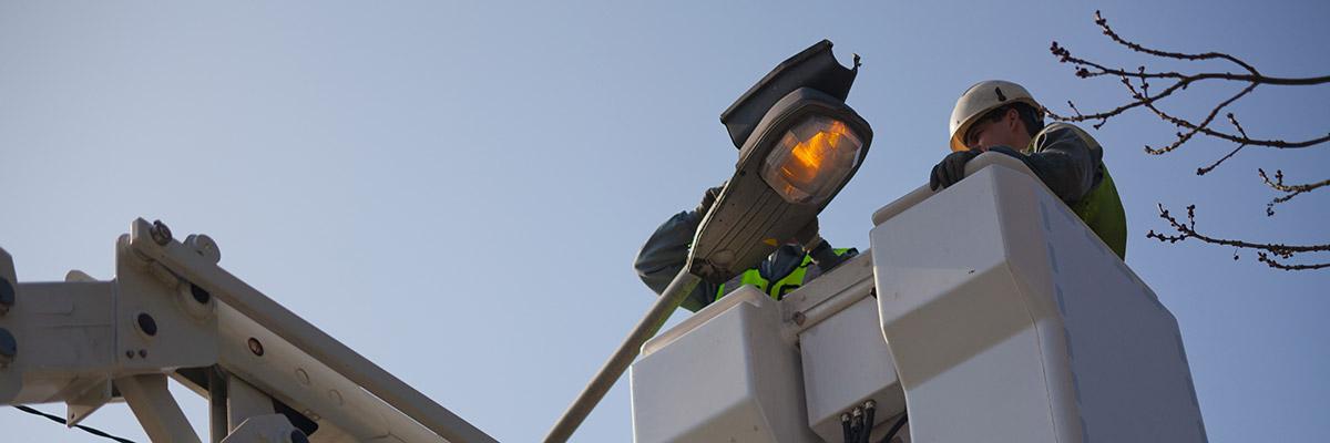 Un technicien ORES est dans une nacelle pour réparer un luminaire en panne