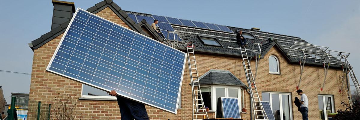 des hommes sont en train d'installer des panneaux solaires sur le toit d'une maison