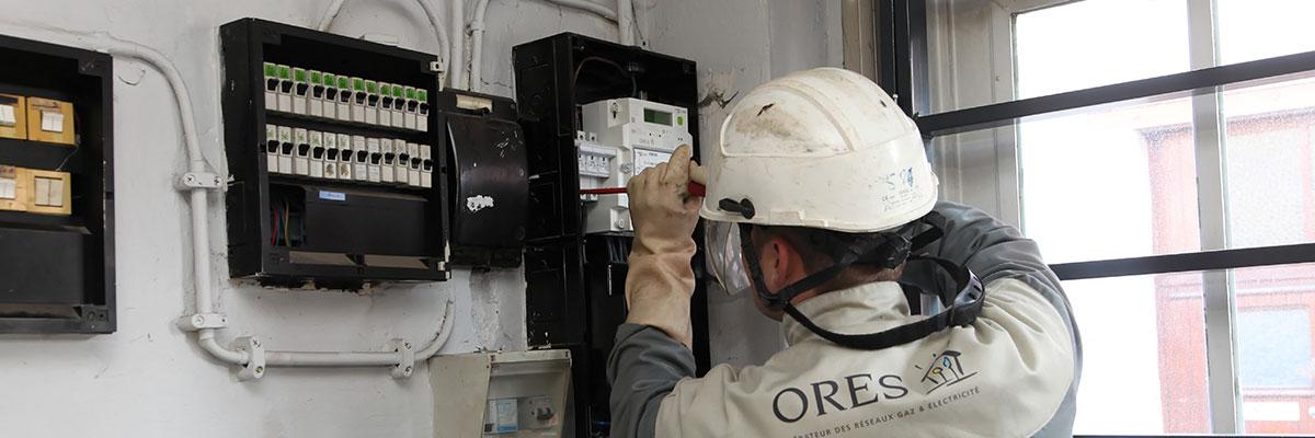 technicien ORES en train de travailler sur un compteur électrique