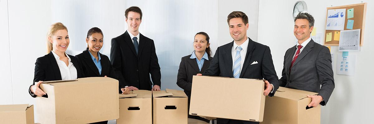 une équipe d'hommes et de femmes en costume transportent des caisses de déménagement
