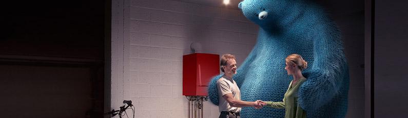 un chauffagiste et une cliente se serrent la main devant une chaudière, ils sont rassemblés par un ours bleu