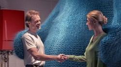 Un chauffagiste et une cliente se serrent la main en souriant devant une chaudière gaz. Ils sont réunis grâce à un grand ours bleu.