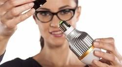une jeune femme s'apprête à visser une ampoule
