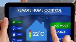 une main appuie sur le bouton mode éco d'une tablette de gestion domotique
