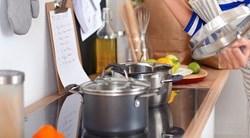 Une jeune femme lit des instructions dans sa cuisine en tenant le couvercle d'une casserole