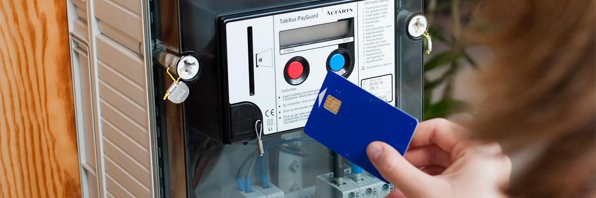 une personne s'apprête à insérer une carte dans un compteur à budget