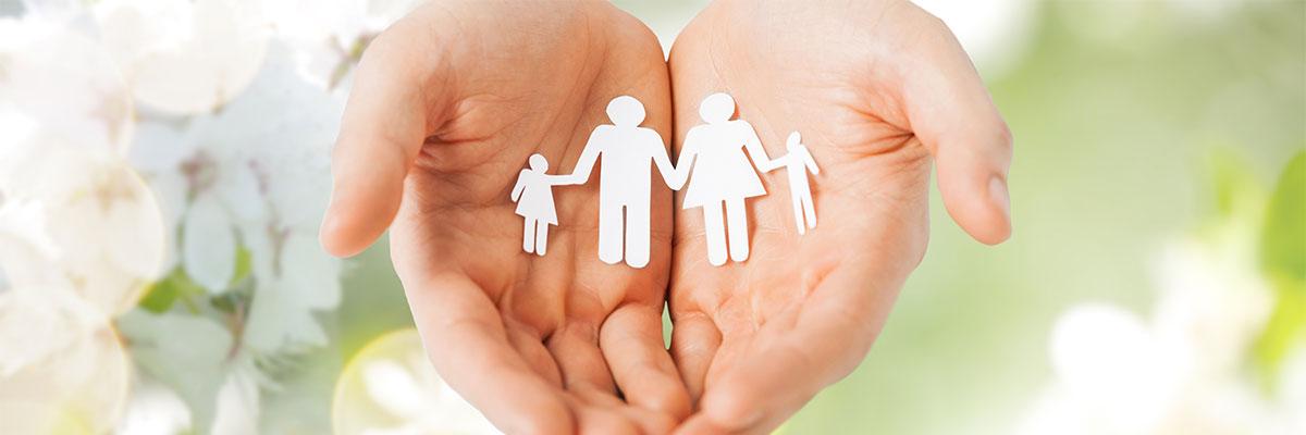 des mains ouvertes tiennent un papier découpé en forme d'une famille