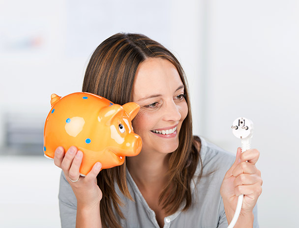 femme avec une tirelire et une fiche électrique satisfaite de ses économies