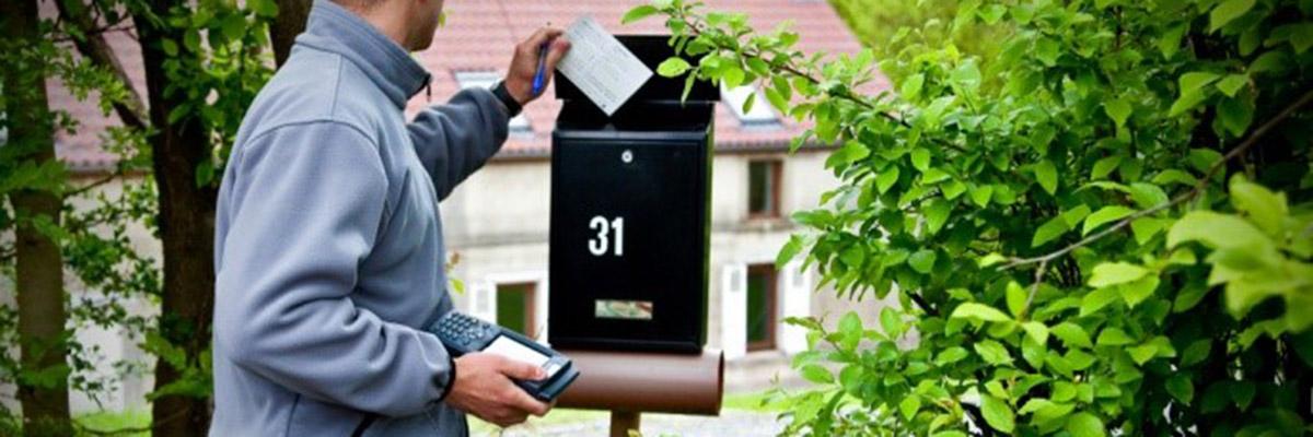 un collaborateur ORES dépose un avis de passage dans une boite aux lettres
