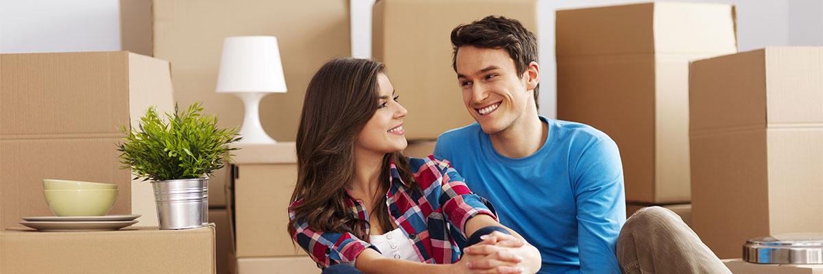 un jeune couple se regarde en souriant, ils sont entourés de caisse de déménagement