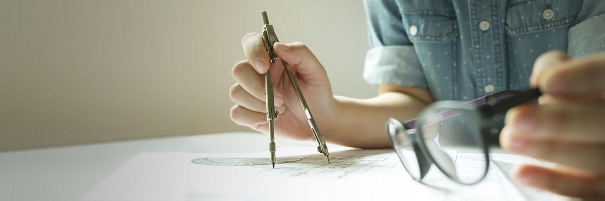un dessinateur architecte tient un compas sur des plans